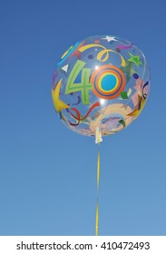 Decorative balloon with the number forty on it. Clear blue sky in the background.