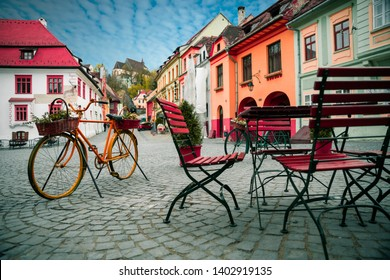 Decorative bicycle next to cafe bar with Stone paved old street and colorful buildings in city center, Sighisoara, Transylvania, Romania, Europe