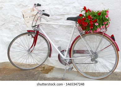 Decorative bicycle, wooden crate and  basket with red pink Apulian Impatiens flowers in front of white Trullo house, Alberobello, Bari, Puglia, Italy