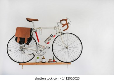 Decorative bicycles hanging on white wall.