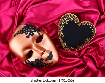 Decorative black heart and mask, on color fabric