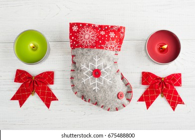 Decorative boot, bows and red green lit candles in christmas composition on white background. Top view