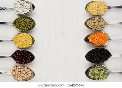 Decorative border of assortment different beans in  spoons with copy space on white wood background. Top view, closeup.