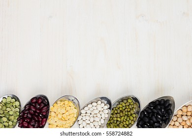 Decorative border of assortment pulses beans in  spoons with copy space on white wood background. Top view, closeup.