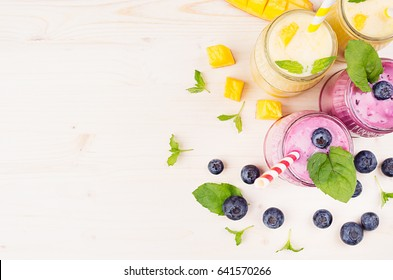 Decorative border of yellow and violet  fruit smoothie in glass jars with straw, mint leaves, mango slices, berry, top view. Soft white wooden board background, copy space.
