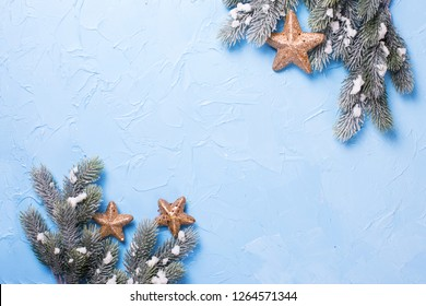 Decorative branches fir tree and golden stars  on blue textured  background. Selective focus. Place for text. View from above. Flat lay.