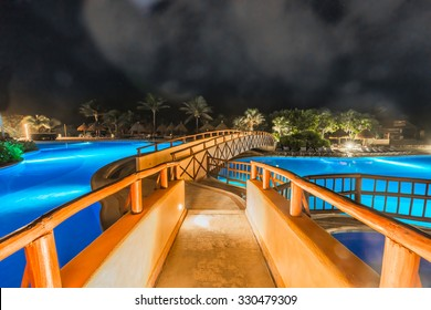 Decorative bridge over the swimming pool of a  luxury caribbean, tropical resort, hotel at night, dawn time.