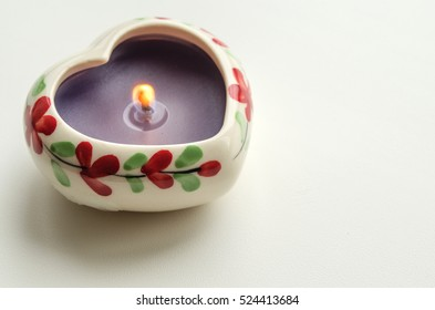 decorative burning candle in the shape of a heart on a light background