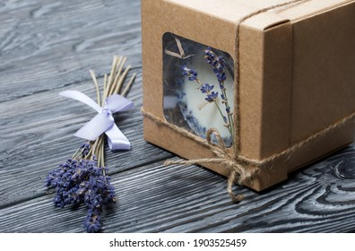 Decorative candle in craft packaging. Tied with a cord and decorated with lavender branches.