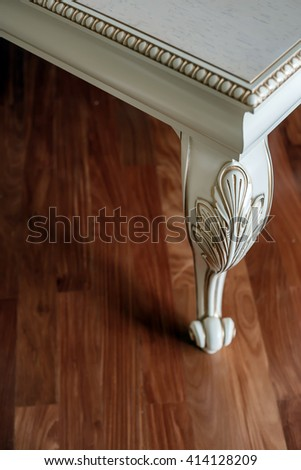 Decorative Carving Table Leg. On A Wooden Floor. Furniture In Classic  Style. White