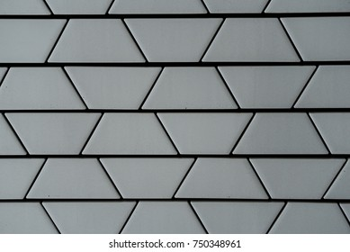 Decorative ceramic bricks in trapezoid shape forming part of exterior wall with visible gaps