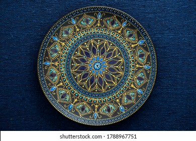 Decorative ceramic plate with black, blue and golden colors, painted plate on background of fabric, closeup, top view. Decorative porcelain plate painted with acrylic paints, handwork, dot painting