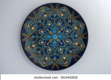 Decorative ceramic plate with black, blue and golden colors, painted plate on white background, closeup, top view. Decorative porcelain plate painted with acrylic paints, handwork, dot painting