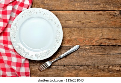 Decorative ceramic plate, fork and red checkered tablecloth on left side on old vintage wooden table background - top view