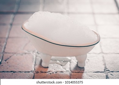 Decorative ceramic tub with foam on legs, selective focus