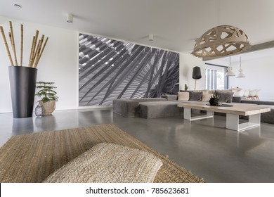 Decorative chandelier above designed table in living room with grey mural on wall