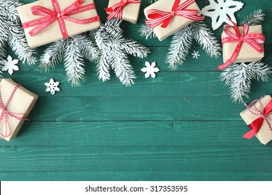 Decorative Christmas background with gifts tied with red ribbon amongst fresh pine branches with scattered snowflake ornaments on a green wooden table with copyspace for your greeting