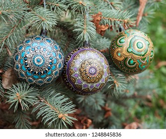 Decorative christmas balls painted with mandalas hanging on the pine tree branches. New Year background