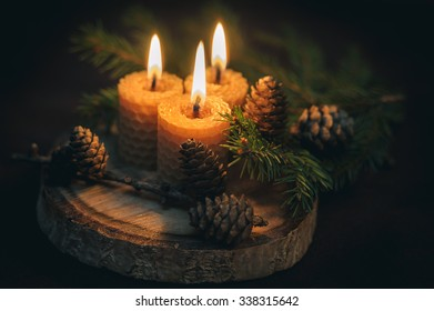 Decorative christmas composition with burning candles on wood in dark