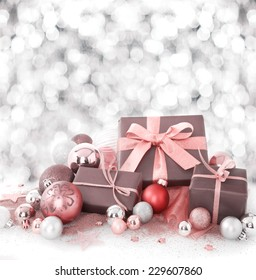 Decorative Christmas gift arrangement with gift-wrapped boxes tied with salmon pink ribbon amongst Xmas baubles on a background bokeh of falling snow with copyspace for your seasonal greeting
