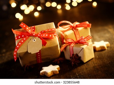 Decorative Christmas gifts tied with red ribbons and bows lying on a wooden table with star ornaments against a sparkling bokeh of party lights behind