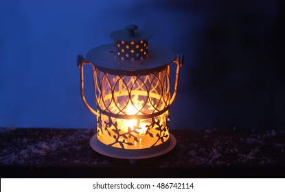 Decorative Christmas lantern with burning candle in a winter park on snow background. New year festive card, poster, postcard design. Night party, home comfort concept.