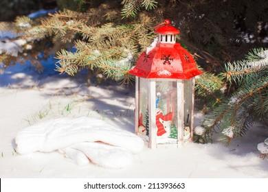 Decorative Christmas lantern near fir branch in snow winter day