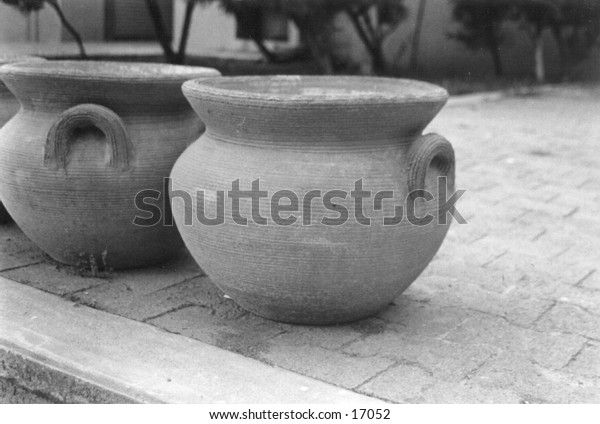 A decorative clay flowerpot with handles.