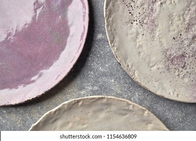 Decorative clay plates covered with glazed on a gray background with place for text. Traditional decorative ceramic handcrafted. Flat lay