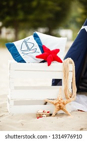 Decorative composition in marine style. Decorative cushion, sea stars, pillows and anchor. Beach holidays and vacation, relax