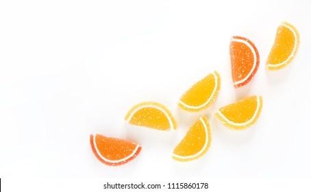 Decorative composition of marmalade candy in shape of citrus fruits wedges. Yellow and orange Jelly sweet candies on white background. Beautiful Web banner With Copy Space. Top view. Flat lay