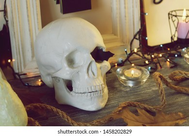 Decorative composition of the skull, pumpkins, lit candles, illumination, leaves and mystical decor on a gray wooden table and a light background, Halloween, autumn, October