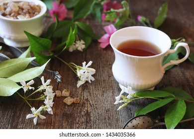 Decorative composition of vintage style: romantic tea drinking with jasmine tea on wooden background