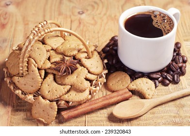 Decorative cookies in wicker basket and cup of hot coffee on old wooden table