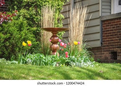 A decorative copper birdbath surrounded by colorful tulips and grasses on a beautiful spring day.