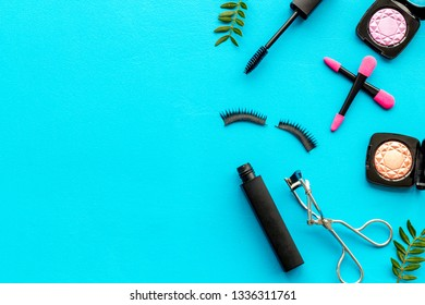 decorative cosmetic set with lash curler and mascara on blue woman desk background top view mock up