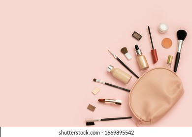 Decorative cosmetic set from pink cosmetic bag on light background. Copyspace for your text. Top view, flat lay.