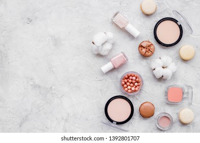 decorative cosmetics for make-up with macaroon cookies on gray stone tabletop background mockup
