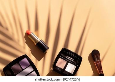 Dekorative Kosmetika für Make-Up- und Sonnenschirme aus tropischem Blatt auf beigem Hintergrund, flach, Laienansicht. Augenschatten, roter Lippenstift, Schminkpinsel. Schöne Mode, Sommerhintergrund. Make-up-Produkte