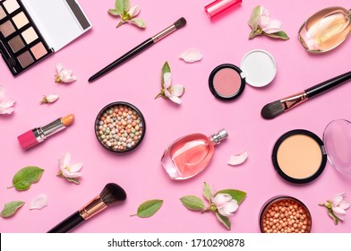 Decorative cosmetics mascara powder lipstick eyeshadow blush balls makeup brush perfume blooming spring branches on pink background top view Flat lay. Beauty blogger concept. Fashion background - Shutterstock ID 1710290878