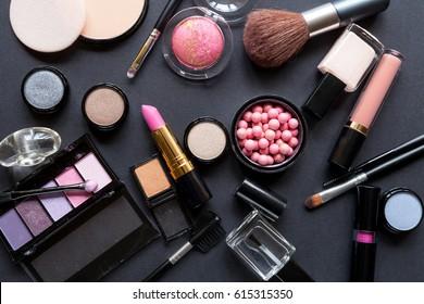 Decorative cosmetics on dark background, top view
