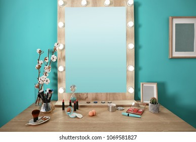 Decorative cosmetics and tools on dressing table near mirror in makeup room