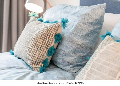 Decorative cozy pillows on a bed and the night lamp