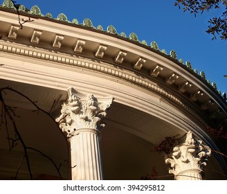 Decorative cresting, dentils, Corinthian columns and more adorn the roof line and facade of a curved porch on a beautiful old Victorian era home.