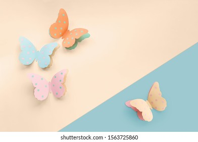 Decorative cute colorful paper butterflies. Top view, copy space for your text on a blue and beige background. Beautiful desigh for Birthday, March 8, Valentine's Day