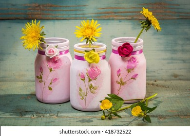 Decorative decoupage jars and flowers on table on bright wooden background