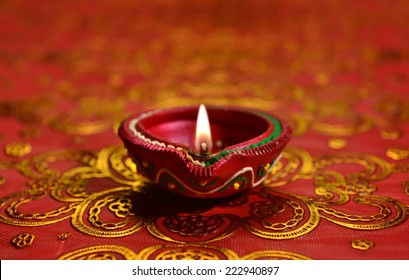 A decorative Diwali lamp against glittering background