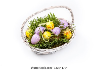 Decorative Easter eggs in a basket with grass