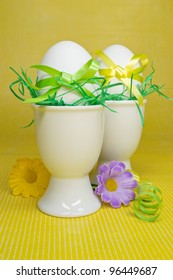 Decorative Easter eggs in egg cups with bows and flowers