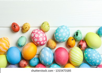 Decorative Easter eggs on white wooden background, space for text. Top view